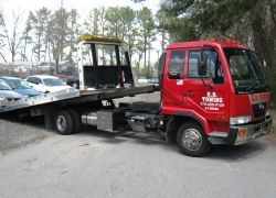 Flatbed Tow Truck with deck tilted for ramp loading