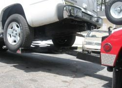 Wheel Lift Tow Truck with hydraulic lifting and winch for vehicle recovery services.